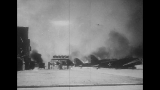 UNITED STATES 1940s: Naval air base bombed by planes / Air base on fire.