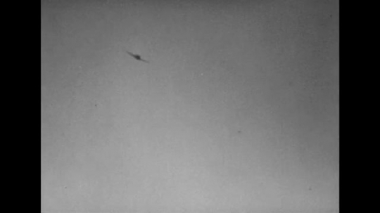 UNITED STATES 1940s: Views of planes flying, firing guns / Soldier hit by gunfire / Panning shot of plane overhead / Soldier fires machine gun.