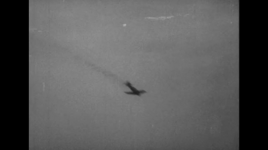 UNITED STATES 1940s: Plane falls, smoking / Plane crashes / Ship in harbor explodes / Views of planes flying / Close up of soldier firing machine gun.