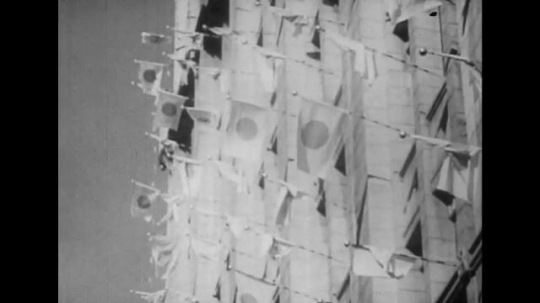 UNITED STATES 1940s: Japanese flags on side of building / People waves flags out of windows / Views of crowd waving flags.