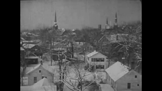 UNITED STATES 1940s: High angle view of snow-covered town / Snow-covered street / Snowplow drives toward camera.