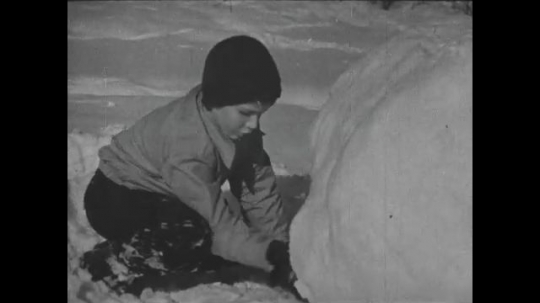 UNITED STATES 1940s: Boy shapes snowball / Kids lift snowball to make snowman / Boy stands up.