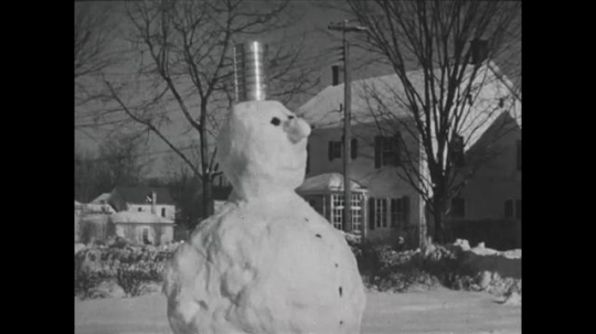 UNITED STATES 1940s: View of snowman / Kids bow to snowman, fade out / Kids march in snow.