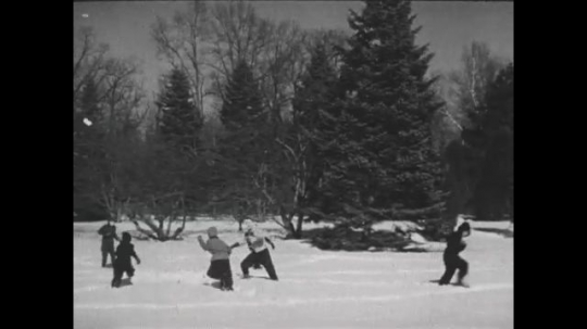 UNITED STATES 1940s: Kids play game in snow / Closer view of kids playing.