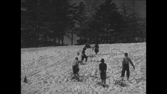UNITED STATES 1940s: Kids pull sleds up hill / Kid sleds down hill.
