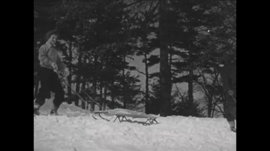 UNITED STATES 1940s: Kids pull sleds in snow, boy positions sled / Boy gets behind sled.