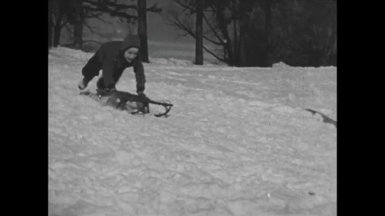 UNITED STATES 1940s: Boy sleds down hill / Kids stand, run up hill.