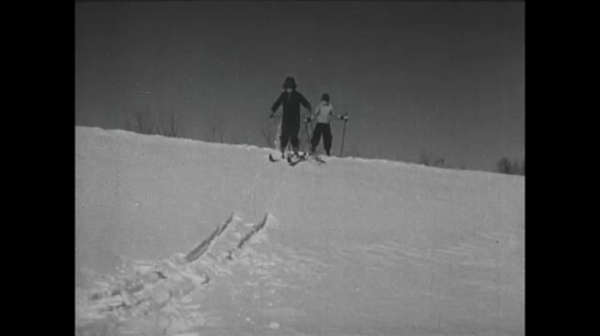 UNITED STATES 1940s: Girl skis down hill / Boy skis down hill, falls.