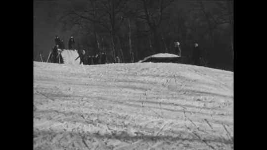 UNITED STATES 1940s: Panning shots of skiers going over jumps.