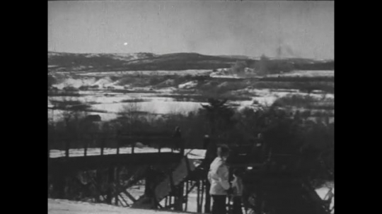 UNITED STATES 1940s: Long shot, skier on ramp / Skier goes over jump / View from hill, skiers go down hill / Kids walk next to damn, carry skis.