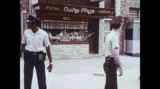 UNITED STATES 1970s: Police officers walk to car, zoom in on light on police car.