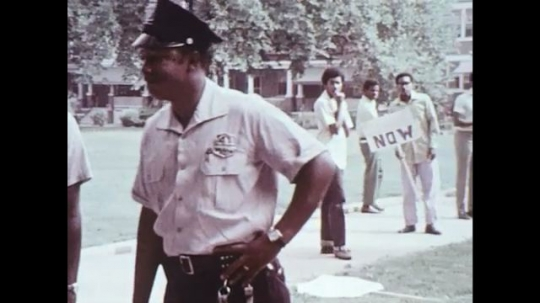 UNITED STATES 1970s: Group of boys walking from police, boy yells and walks away, zoom in on abandoned protest sign.