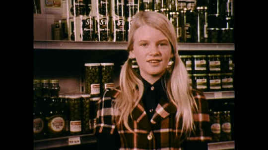 UNITED STATES: 1970s: girl stands by shelf in supermarket. Girl talks to camera.