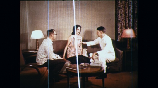 UNITED STATES: 1960s: medic comforts lady in home. Men help lady to feet. Medic examines pregnant lady.