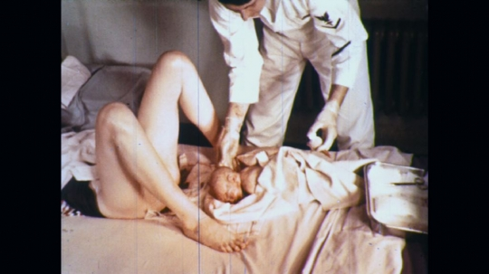 UNITED STATES: 1960s: medic picks up umbilical cord for examination
