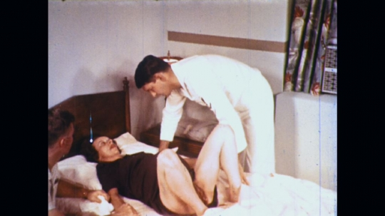 UNITED STATES: 1960s: medic comforts lady in labour at home. Medic prepares delivery kit.