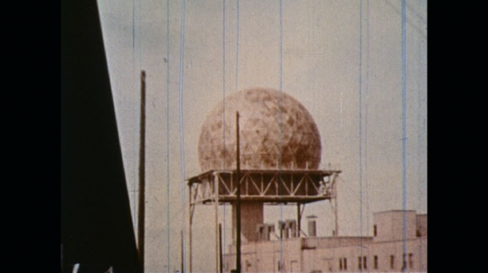 UNITED STATES: 1970s: close up of glass dome. Inside of satellite dome. Man answers phone
