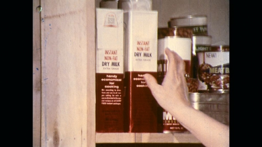 UNITED STATES: 1970s: lady takes carton of milk from shelf. Lady pours powdered milk into jug. Lady mixes milk from powder. Girl drinks mil