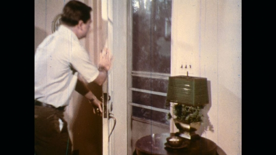 UNITED STATES: 1970s: man closes doors. Lady covers windows of house. Girl helps mother with foil on windows