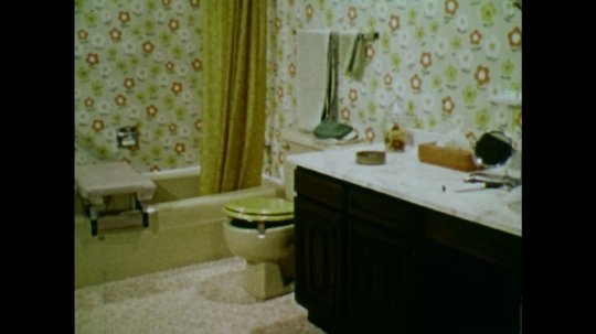UNITED STATES: 1970s: view of bathroom. Man in wheelchair in bathroom. Man removes footplates from wheelchair.