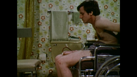 UNITED STATES: 1970s: man moves wheelchair towards bathroom seat. Man moves legs. Man moves wheelchair forward