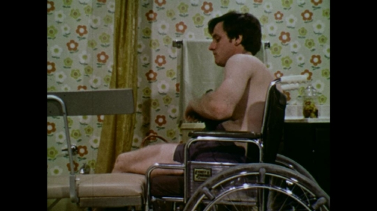 UNITED STATES: 1970s: man picks up towel from rail. Man transfers from wheelchair to bath seat.