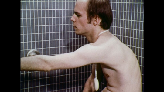 UNITED STATES: 1970s: man washes hair with shower hose and shampoo.