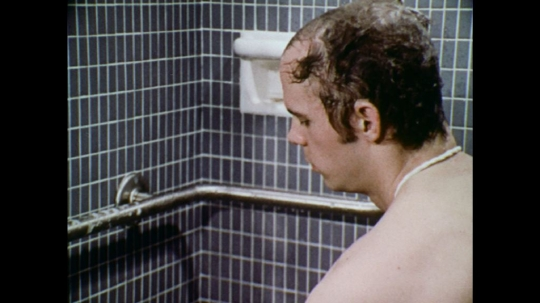 UNITED STATES: 1970s: man washes hair with shower hose and shampoo. Man rinses shampoo from hair.