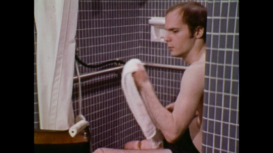 UNITED STATES: 1970s: man puts towel on back of wheelchair. Man puts towel on wheelchair seat. Man slides from shower seat to wheelchair seat