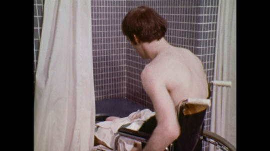 UNITED STATES: 1970s: man reverses wheelchair from shower cubicle.