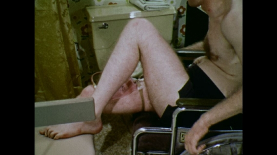 UNITED STATES: 1970s: man reverses wheelchair in bathroom. Man puts footrest in position on chair.