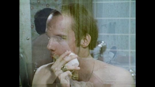UNITED STATES: 1970s: man turns on tap in sink. Man wipes face. Man shakes shaving foam.