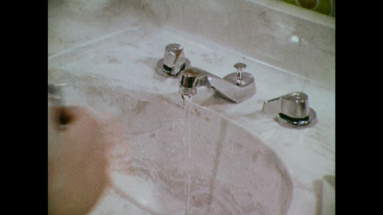 UNITED STATES: 1970s:  man rinses razor under sink tap. Man shaves face. Man rinses face with water. Man dries face with towel.