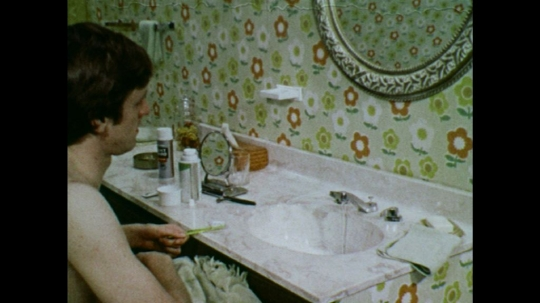 UNITED STATES: 1970s: man cleans teeth in bathroom sink. Man in mirror.