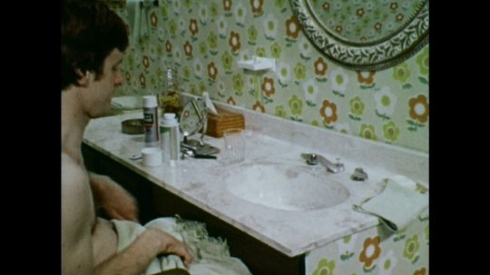 UNITED STATES: 1970s: man wipes face on towel. Man shakes can. Man puts on deodorant.