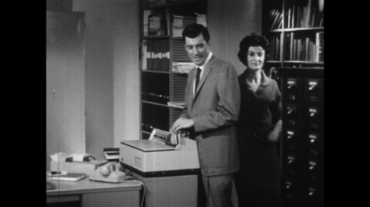 UNITED STATES: 1960s: lady walks to filing cabinet. Lady and man look at notes in cabinet.