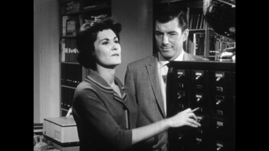 UNITED STATES: 1960s: man helps lady look through filing cabinet during conversation. Lady finds information. Lady writes notes.