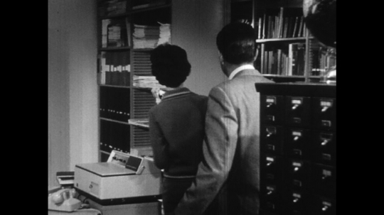 UNITED STATES: 1960s: man talks to lady in office. Lady writes on paper for man.
