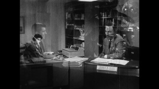 UNITED STATES: 1960s: two men have meeting in office. Man makes telephone call
