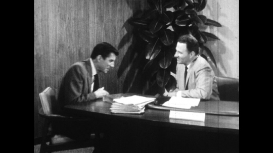 UNITED STATES: 1960s: men shake hands after meeting. Man smiles in corner of room. Man leaves office