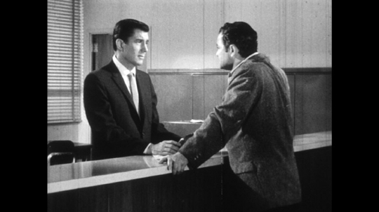 UNITED STATES: 1960s: two men speak at reception desk.