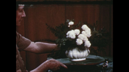 UNITED STATES: 1960s: lady turns flower arrangement on table. Lady puts green branches in arrangement.