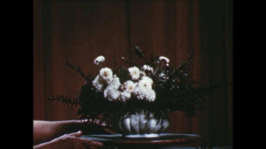 UNITED STATES: 1960s: lady turns finished arrangement on table.