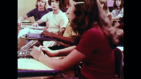 UNITED STATES: 1970s: students have discussion in classroom. Student raises hand. Students leave class. Teacher listens to students