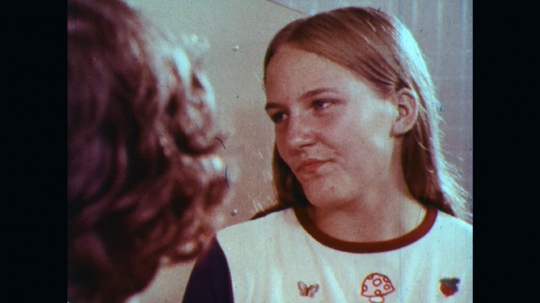 UNITED STATES: 1970s: boy talks to girl by school lockers. Students talk in corridor. Lady puts in earrings