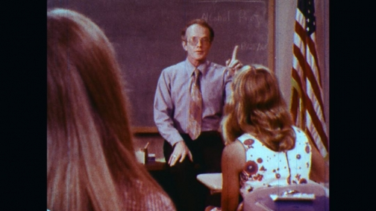 UNITED STATES: 1970s: teacher asks question in class. Students raise hands. Girl talks to teacher