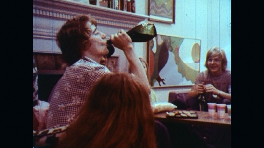UNITED STATES: 1970s: boy drinks from bottle. Friends laugh. Teenagers talk and smile