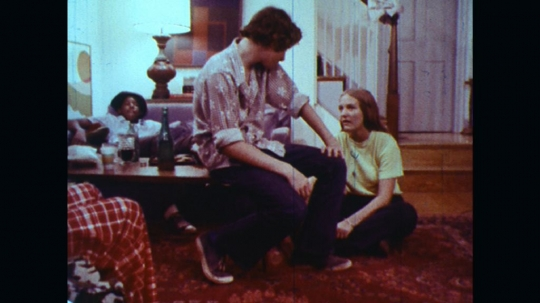 UNITED STATES: 1970s: teenagers talk at party. Boy sits in seat. Girl talks to boy at party