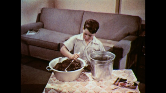 UNITED STATES: 1950s: boy prepares sand for aquarium. Girl and boy add sand to tank