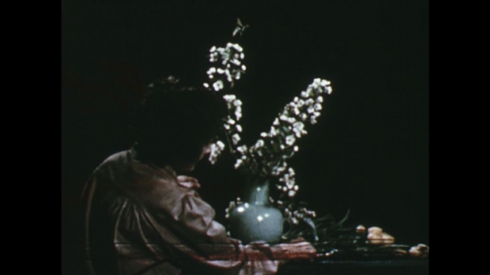 UNITED STATES: 1960s: lady picks up leaf and flower. Lady adds flowers to arrangement.